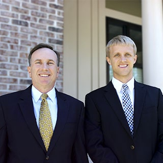 Dr. Laro and Dr. Poston smiling straight for a photo in front of our dental office next to a brick wall