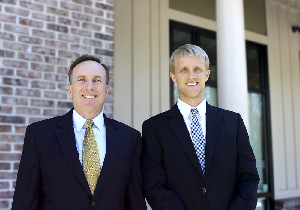 Our first-class Charleston periodontists, standing side by side and smiling