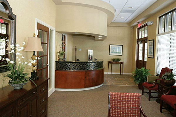 Our comfortable waiting room with a wooden front desk and nice chairs