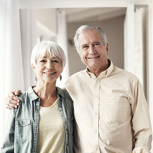A happy elderly couple smiling while embracing