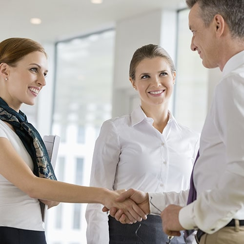 Two people shaking hands while smiling and another woman looking at them and smiling