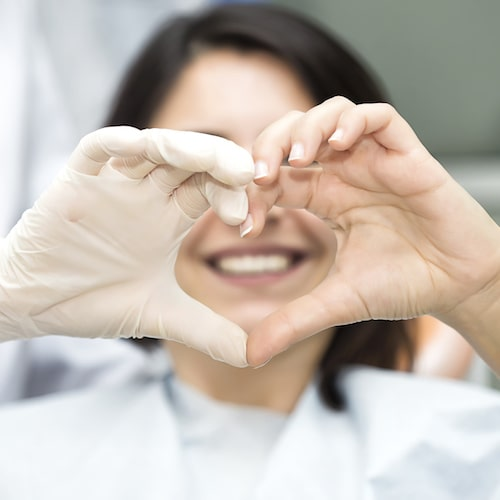 A dentist and patient making a heart shape with their hands
