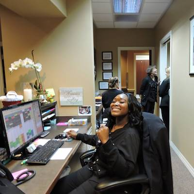 Front of house staff member sitting at the dental reception smiling