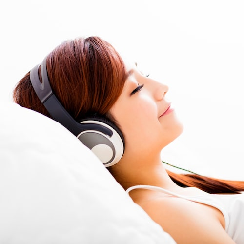 A young girl relaxing with headphones on