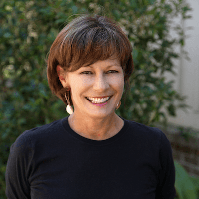 Headshot of Kathy smiling in a black top and short dark hair