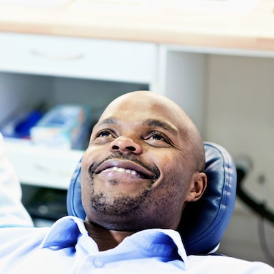 Man sitting in a dental chair and wearing a blue shirt