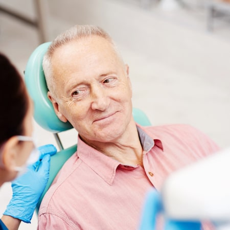Older man in a pink shirt smiling at the dental assistant