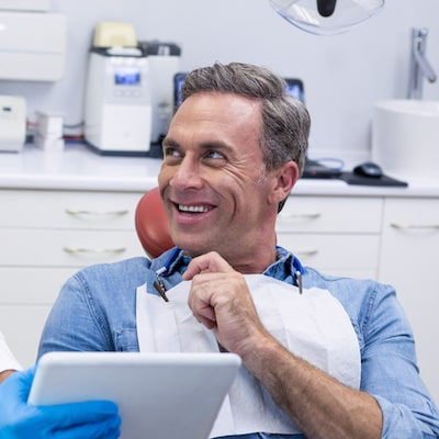 A man in a dentist chair looking to his right and smiling