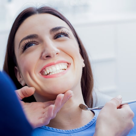 Headshot of a women smiling in dental chair with dentists hand in shot