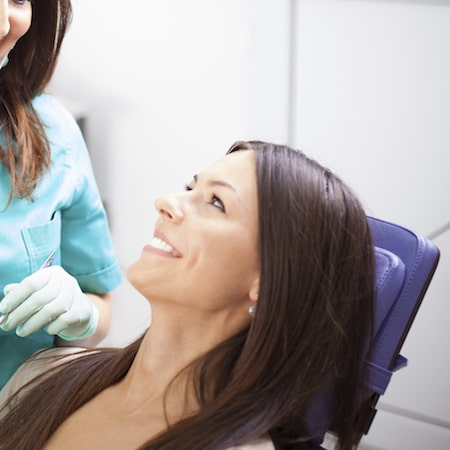 Profile of a women looking at the dental assistant smiling