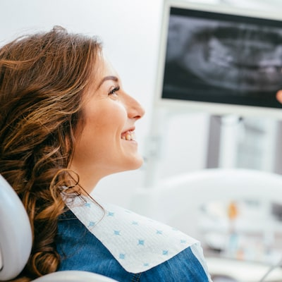 Women in dental chair smiling with x-rays in the background