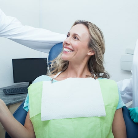 Women looking at her dentist smiling wearing a green and white dental bib