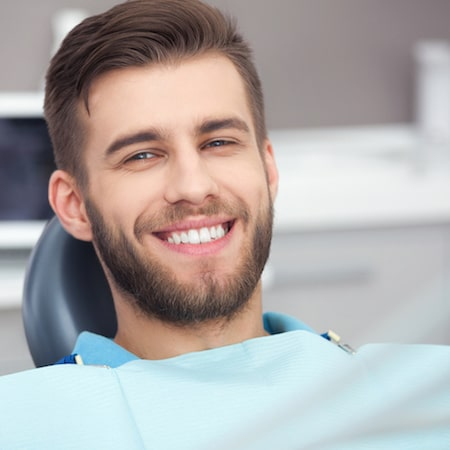 Headshot of young man smiling with blue dental bib on